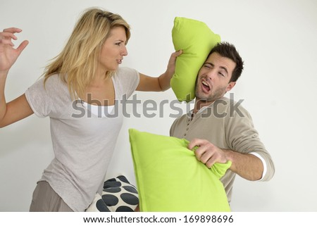 Angry couple throwing pillows at each other - stock photo