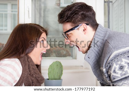 angry couple yelling at each other shouting face to face - stock photo