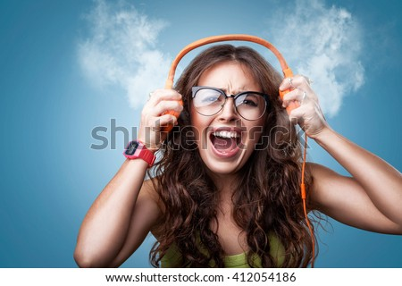 Angry crazy girl in headphones listening to music and screaming loud blowing white smoke coming out of ears. Closeup portrait girl on blue background. Negative human emotion facial expression feeling - stock photo