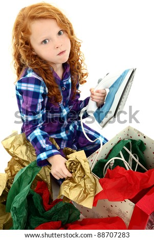 Angry dissappointed girl child receiving an iron as a gift.  Over white background. - stock photo