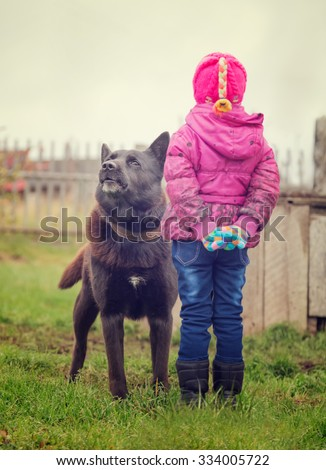 Angry dog stares at a fearless child. - stock photo