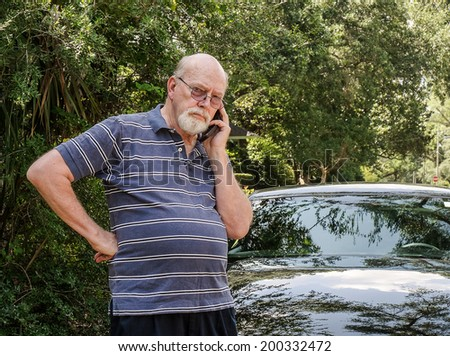 Angry elderly man on cell phone calls for roadside assistance for car malfunction or breakdown emergency. - stock photo