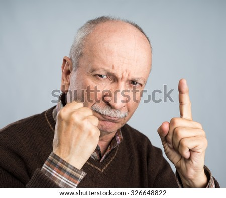 Angry elderly man pointing up on a dark background