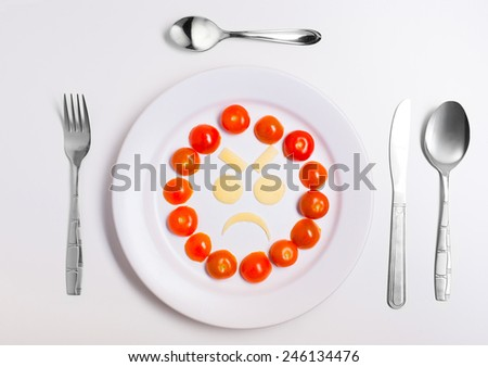 angry emoticon food, made from cheese and tomatoes, on a plate with cutlery, isolated