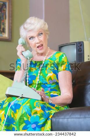 Angry European senior female on phone in 1960s fashion - stock photo