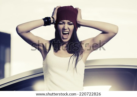 Angry fashion woman shouting at the car  - stock photo