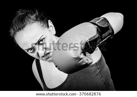 Angry female boxer throwing punch. Black and white. - stock photo