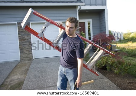 Angry, frowning man standing in front of house holding ladder and hammer. Horizontally framed photo. - stock photo