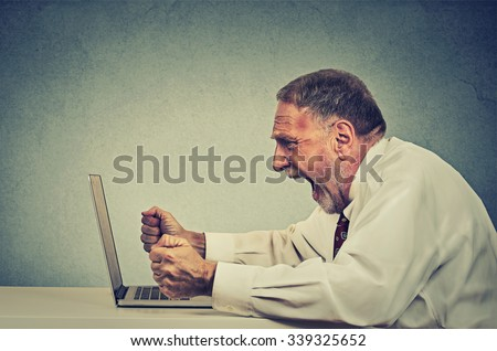 Angry furious senior business man working on computer, screaming. Negative human emotion facial expression feeling aggression anger management issues concept. Side profile guy having nervous breakdown
