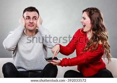Angry furious wife shouting at husband showing text messages from lover mistress on his mobile phone. Outraged girlfriend find out about boyfriend affair romance betrayal. Cheating man covering ears. - stock photo