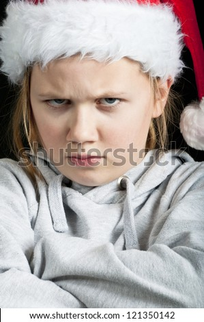 Angry girl wearing a christmas hat - stock photo