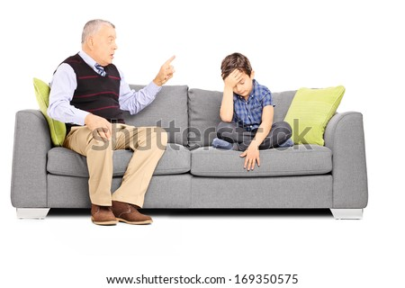 Angry granddad shouting at his sad nephew, seated on a sofa, isolated on white background