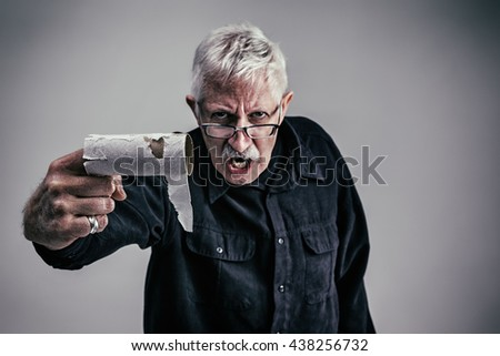 Angry Grandpa holding an empty toilet paper roll on his finger while looking disgusted - stock photo