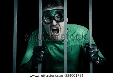 Angry green superhero shouting behind prison steel bars. - stock photo