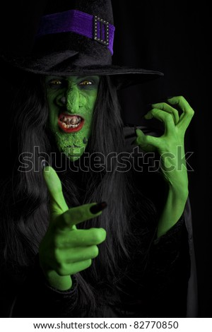 Angry green witch, black background. - stock photo