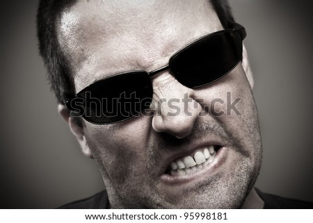 Angry guy in sunglasses - stock photo