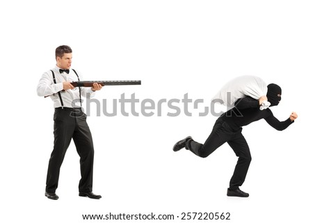 Angry guy with rifle shooting at a burglar with a stolen bag isolated on white background - stock photo