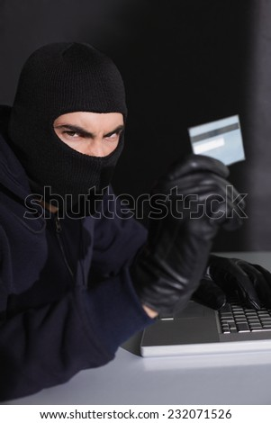 Angry hacker using credit card and laptop on black background - stock photo
