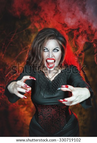 Angry halloween beautiful vampire with long nails holding out hands