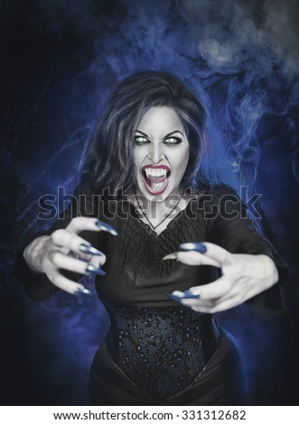 Angry halloween beautiful vampire with long nails holding out hands - stock photo