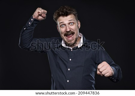Angry happy bearded man punch his enemies looking straight to the camera.    - stock photo