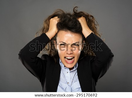 Angry hispanic businesswoman shouting and pulling her hair - stock photo
