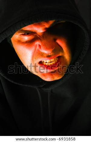 Angry hooded male looking at you with a slight bit of contempt. - stock photo