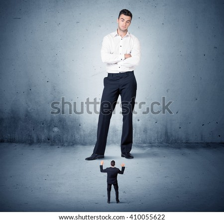 Angry huge business man lokking at small coworker guy concept on background - stock photo