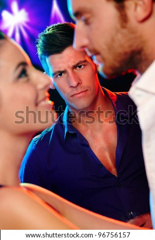 Angry jealous man looking at young dancing couple in nightclub.? - stock photo