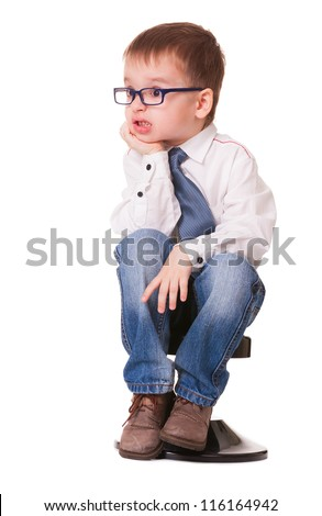 Angry kid in shirt and jeans sits on small chair, on white background - stock photo