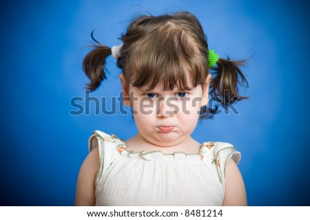 Angry kid on blue background - stock photo