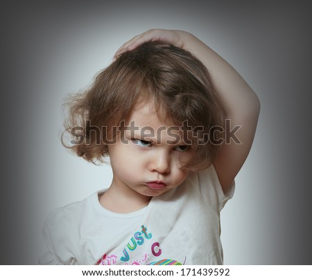 Angry kid on grey background. Closeup portrait - stock photo