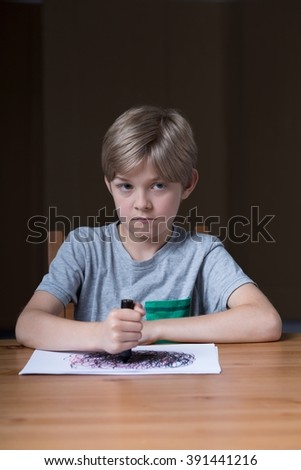 Angry little boy drawing with black pencil - stock photo