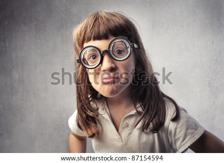 Angry little girl with thick eyeglasses - stock photo