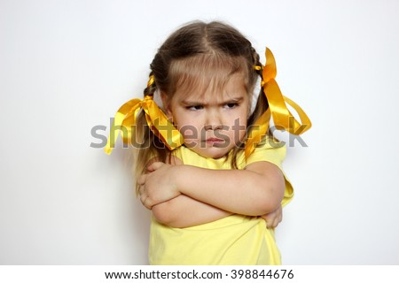 Angry little girl with yellow bows and yellow T-shirt over white background, sign and gesture concept - stock photo