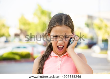 Angry mad child, girl screaming on mobile phone, isolated outdoors background. Negative human face expressions, emotions, feelings, attitude - stock photo