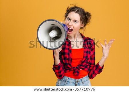 Angry mad young woman in plaid shirt screaming in megaphone over yellow background - stock photo