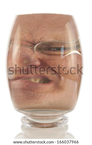 Angry male face locked up in vacuum of glass bell - stock photo