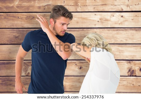 Angry man about to hit his girlfriend against wooden planks background - stock photo