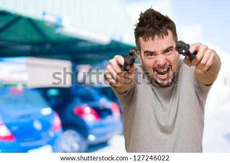 angry man aiming with guns at a car park - stock photo