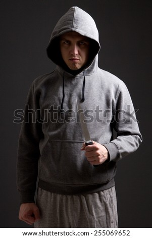 angry man criminal with knife over grey background - stock photo