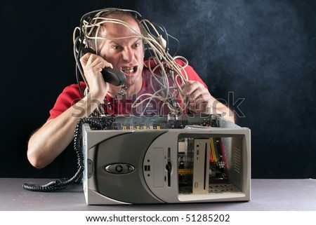 angry man having problem with his computer calling support on phone - stock photo