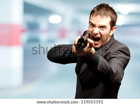 Angry Man Holding Gun in a garage - stock photo