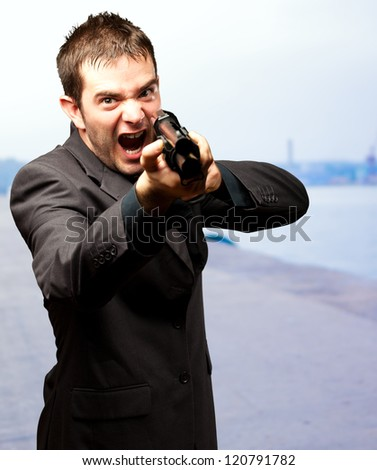Angry Man Holding Gun, outdoor - stock photo