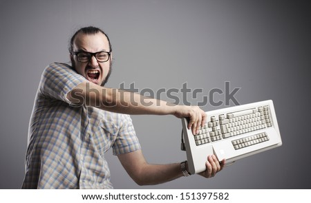 Angry man is destroying a keyboard - stock photo