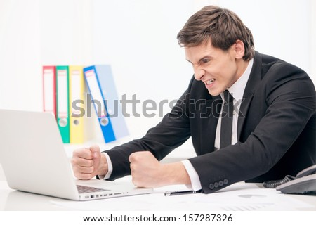 Angry man looking at laptop - stock photo