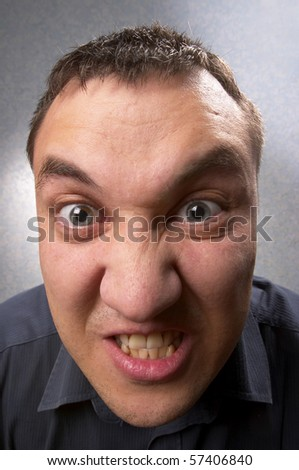 Angry man portrait over light defocused background (wide angle lens shot)