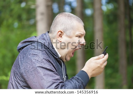Angry man screaming in phone - stock photo