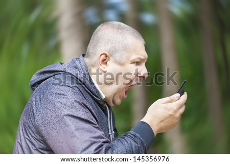 Angry man screaming in phone on the rotating background - stock photo