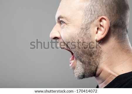 angry man screaming isolated on gray background with copyspace - stock photo